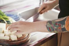 Woman chopping tofu in kitchen with ornate tattooed arm Stock Photos