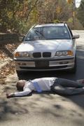 Man lying down on a road in front of a car - stock photo