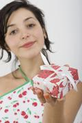 Woman looking at camera and holding present Stock Photos