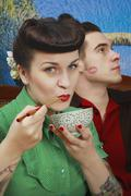 Lähikuva nuori rockabilly, nainen, jolla keitto kulhoon ja syömäpuikot Kuvituskuvat