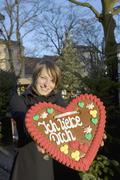 Woman holding a heart-shaped gingerbread cookie Stock Photos