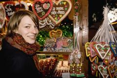 Woman standing at a market stall with heart-shaped gingerbread cookies, Berlin, - stock photo