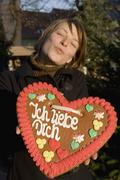 Woman holding a heart-shaped gingerbread cookie and puckering her lips Stock Photos
