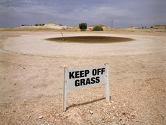Keep off grass sign in front of barren landscape Stock Photos