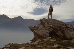 Man standing on a rocky ledge and looking at the mountains Stock Photos