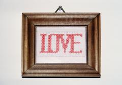 Love cross-stitching in a frame and hanging on a wall Stock Photos