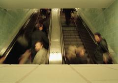 People moving up escalators at a train station Stock Photos