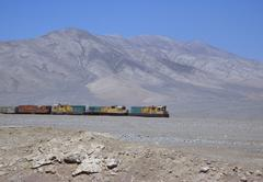 Freight train moving through barren landscape Stock Photos