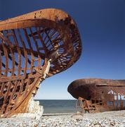 Two rusted ships on a pebble beach Stock Photos