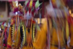 Men dancing in traditional clothing and feather headdresses - stock photo