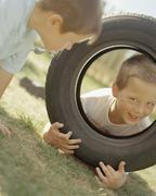 Children playing with tire - stock photo