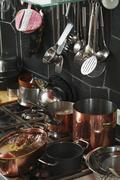Kitchen utensils around a stove Stock Photos