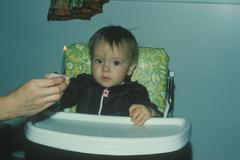 Young boy sitting in a highchair in front of a cupcake with a lit candle Stock Photos