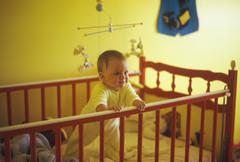 Baby boy standing up in his crib Stock Photos