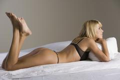 Woman lying on a bed wearing lingerie - stock photo