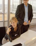 A young woman sitting at an office desk and pointing as a young man stands - stock photo