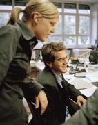 Office colleagues gathered at a desk Stock Photos