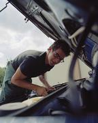 Young man checking a car battery - stock photo