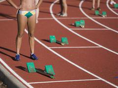 Women standing behind starting blocks at the beginning of a race Stock Photos
