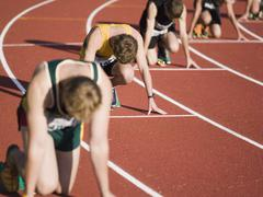 Group of male athletes in starting blocks on a running track - stock photo