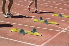 Stock Photo of Men standing behind starting blocks at the beginning of a race