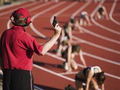 Kilpailu virkamies, jolla on lähtölaukaus alussa juoksulaji Kuvituskuvat