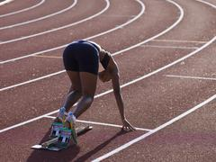 Female athlete in starting blocks on a running track - stock photo
