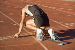 Male athlete in starting blocks on a running track - stock photo