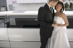 Bride and groom standing together in front of a stretch limousine - stock photo