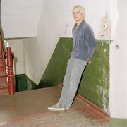 A young man leaning against a wall in a stairwell Stock Photos