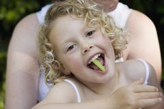Young girl sitting on her mother's lap with a piece of celery in her mouth - stock photo