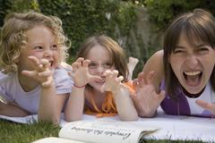 A woman and two girls growling whilst lying down in a backyard - stock photo