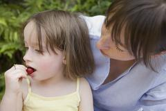 A mother looking at her daughter eating Stock Photos