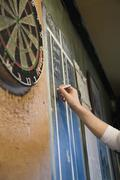 Person keeping score on a blackboard during a game of darts Stock Photos