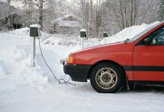 Power cable connected to a parked car in the winter Stock Photos