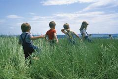 Rear view of four children walking through a field - stock photo