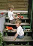 Two young boys playing with toys on steps - stock photo