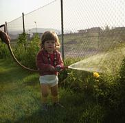 Young girl watering the garden witha hosepipe - stock photo