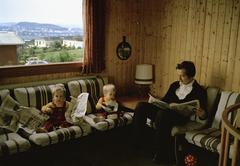 Two toddlers reading the newspaper with father - stock photo