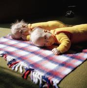 Two babies lying on rug Stock Photos