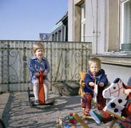 Two toddlers playing on rocking horses on balcony Stock Photos