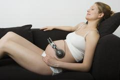 Pregnant woman lying down on a sofa with headphones on her stomach Stock Photos
