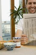 Man reading a newspaper over breakfast - stock photo
