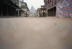 Street scene with rock formation in the distance, Yangshou, China - stock photo