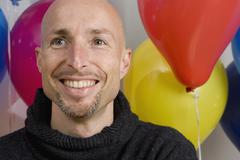 Stock Photo of Man sitting in front of balloons