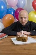 Man sitting at table with birthday cake and balloons Stock Photos