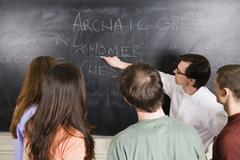 Lecturer writing on blackboard for a group of students - stock photo