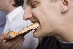 Man eating slice of pizza Stock Photos