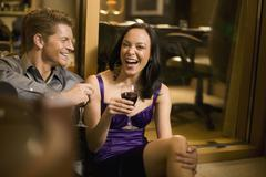 Young couple sitting together in a hotel room and drinking wine - stock photo