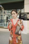 Nainen käyttää matkapuhelinta ja tilalla kukkaro, Rodeo Drive, Los Angeles, Kuvituskuvat